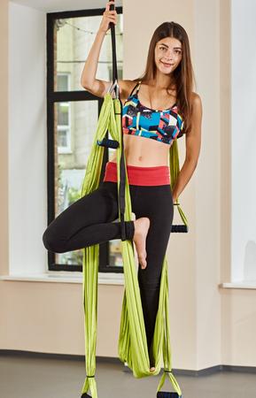 mujer meditando: Joven posando en antigravedad yoga aérea hamaca verde. club de fitness de interior