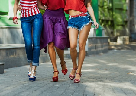 outerwear: only legs three Young pretty girls having  fun, walking at the city. Wearing stylish outerwear