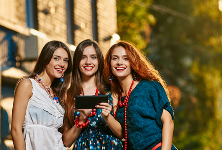 triplet: holidays, tourism, technology and internet - three beautiful girls with tablet pc computer. autumn outdoor
