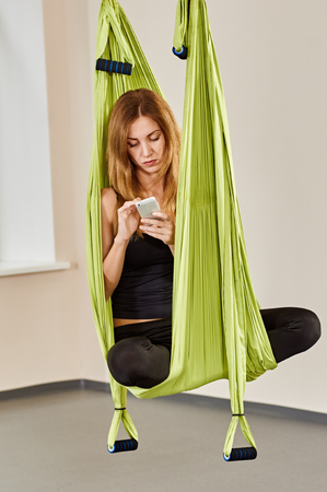 hang body: Young woman posing in anti-gravity aerial yoga green hammock. indoor fitness club. relax with phone Stock Photo