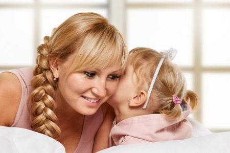 25 29 years: Young mother whispering with her daughter on light window background