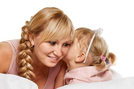 Young mother whispering with her daughter on white background Stock Photo