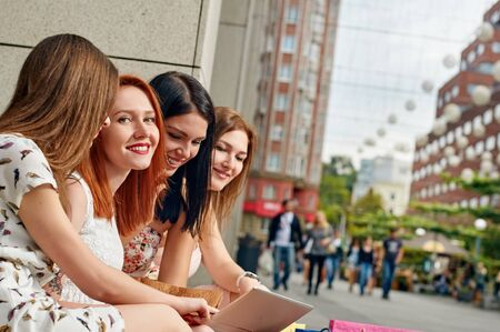 portrait of a women: holidays, tourism, technology and internet - four beautiful girls looking at tablet pc computer. outdoor city Stock Photo