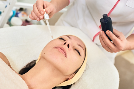 anti ageing: Serum facial treatment of young woman in spa salon