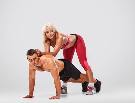 musculine: fitness, sport, training, teamwork and lifestyle concept - man starts out push-ups and woman leaned on his. full length light grey background