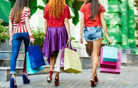 woman hands: beautiful women from back. slender legs. Sexy girl holding a paper shopping bags, outdoor city Stock Photo