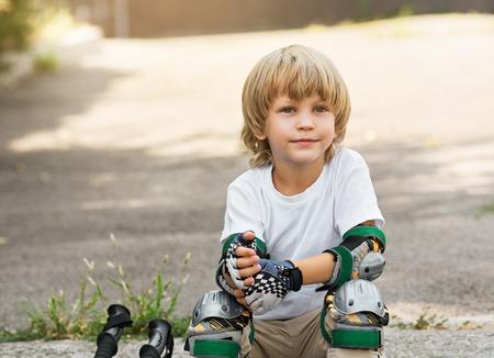 El niño pequeño pone rodillos sentado en el borde de la carretera. tire de guantes protectores