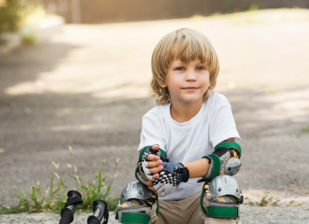 Little boy puts rollers sitting on the roadside. pull on protective gloves Stock Photo