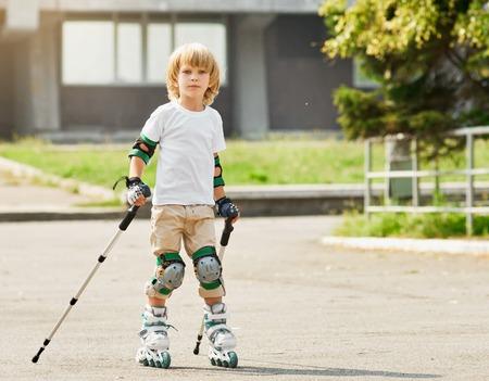 ni�o en patines: ni�o en patines al aire libre. principiante. con bastones de marcha n�rdica