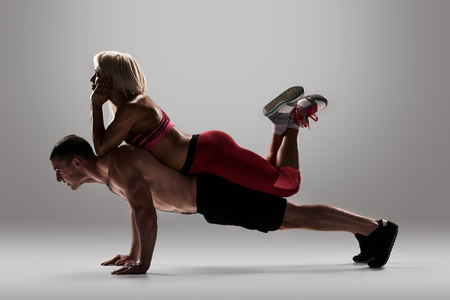 musculine: fitness, sport, training, teamwork and lifestyle concept - man starts out push-ups and girl lying on him and rests. full length grey background