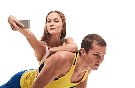 musculine: fitness, sport, training, teamwork and lifestyle concept - man starts out push-ups and girl lying on him and makes selfie.