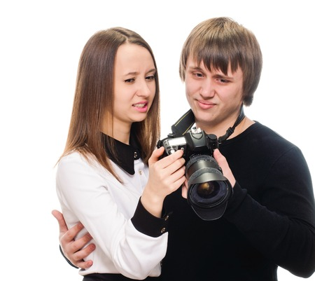 oversight: young couple with camera. reviewing bad shot. Isolated on white
