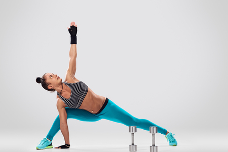 planking: sporty woman planking on the floor on light background Stock Photo