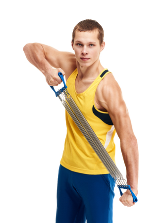 expander: strong athletic guy sports man stretches expander on white