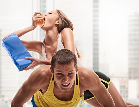 musculine: fitness, sport, training, teamwork and lifestyle concept - man starts out push-ups and girl lying on him and eating. on light window background