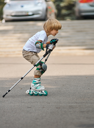 ni�o en patines: young boy on roller skates outdoors.  beginner. with nordic walking poles Foto de archivo