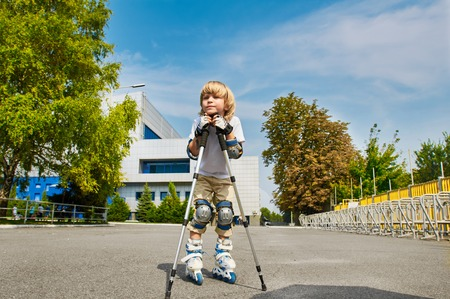 niño en patines: muchacho joven en patines de ruedas al aire libre. principiante. con bastones de marcha nórdica. descanso.