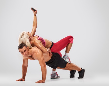 musculine: fitness, sport, training, teamwork and lifestyle concept - man starts out push-ups and girl lying on him and makes selfie. full length light grey background Stock Photo