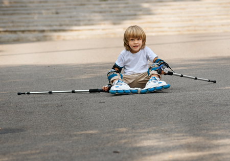 get tired: Young boy wearing skates. he sits on asphalt after fall