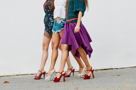 outerwear: only legs three Young pretty girls having  fun, walking about the wall. Wearing stylish outerwear Stock Photo