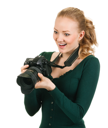 oversight: young woman photographer with camera. reviewing good shot. Isolated on white