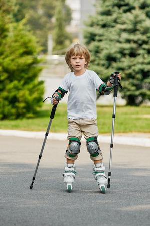 niño en patines: young boy on roller skates outdoors.  beginner. with nordic walking poles Foto de archivo