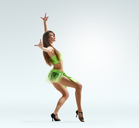 fishnet stockings: young beautiful dancer in bright dress on light studio background Stock Photo