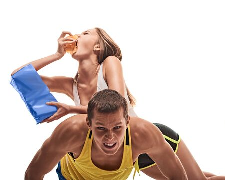 musculine: fitness, sport, training, teamwork and lifestyle concept - man starts out push-ups and girl lying on him and eating. on white background Stock Photo