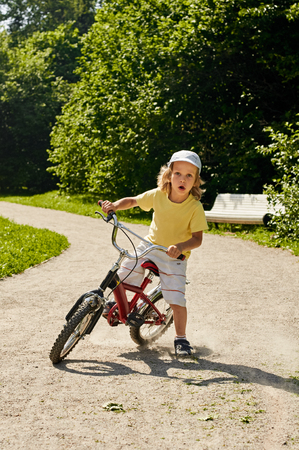 braking: boy with bicycle in park. braking time after. dust from under the wheels Stock Photo