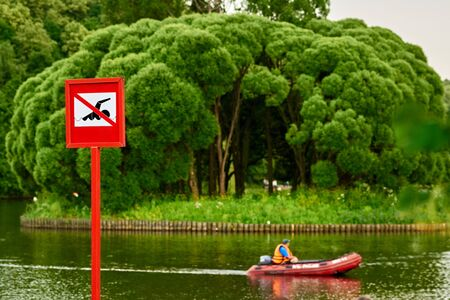 no swimming sign: A no swimming danger sign at the beach. there is distance boat Stock Photo