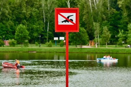 no swimming sign: A no swimming danger sign at the beach. there are distance pedal boats Stock Photo