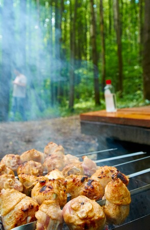 flammable: Barbecue grill with meat close-up, with a bottle of flammable liquid