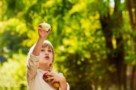 fun activity: portrait of little handsome boy clasps apples by hands, he shows his hand up,  outdoor summer autumn warm Stock Photo