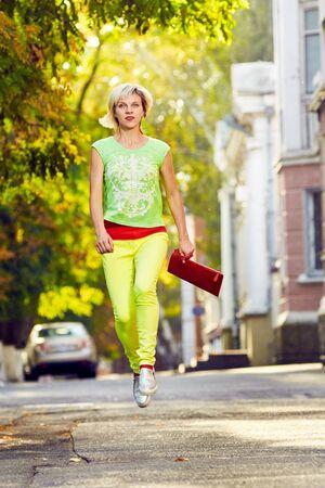 levitation: Beautiful woman walking in the sunshine city street. frozen in a jump. levitation