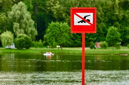 no swimming: A no swimming danger sign at the beach. there are distance buoy pedal boats