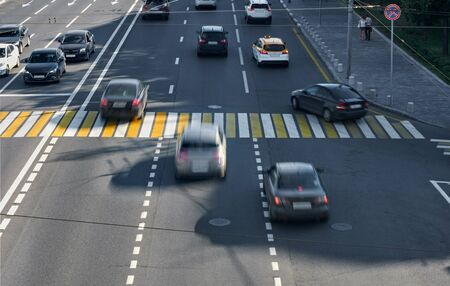 pedestrian crossing: three lanes with a pedestrian crossing, some cars blurred in motion