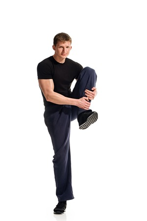 flexed: Young athlete attractive doing fitness exercises, flexed leg. white background