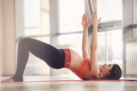 Health concept. Young beautiful pregnant woman does yoga exercise in the modern gym with sunlight in window