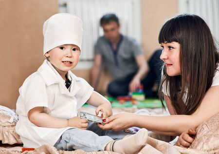 doctor toys: Little beautiful boy in costume of doctor at home with mother. father is on background plays wuth toys Stock Photo