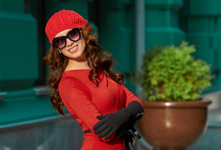 green beret: Beautiful brunette young woman wearing red dress, beret, gloves on green house background