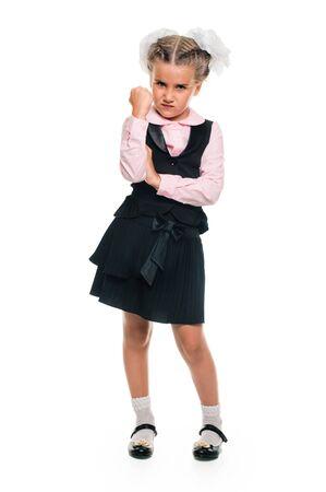 threatens: little Schoolgirl threatens with her fist. full length Stock Photo