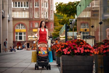 shopping buggy: beautiful young woman pushing baby carriage on street