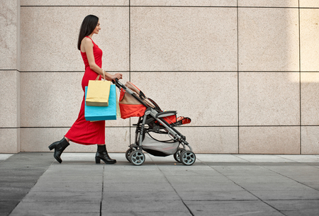shopping buggy: walking young mother with baby carriage along the wall on city street Stock Photo