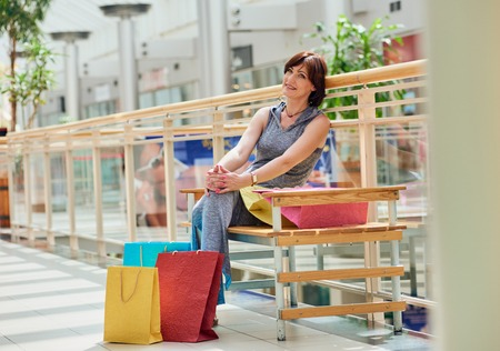 after shopping: Beautiful, happy and fashionable woman with shopping bags at the mall. sitting and relaxing after shopping