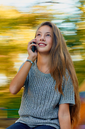 girl having fun on spinning roundabout and using a mobile phone. Autumn. Naturally blur motion Stock Photo