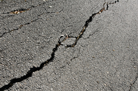 worn: Old worn and cracked asphalt with cracks