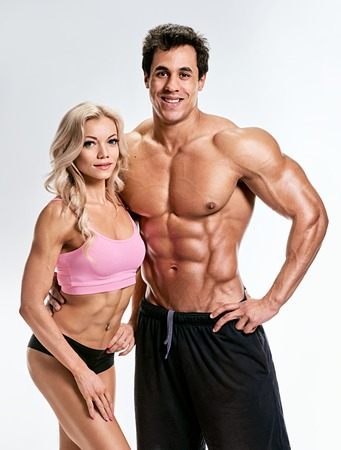 muscle guy: Couple man and woman muscled. bodybuilders portrait on grey background Stock Photo