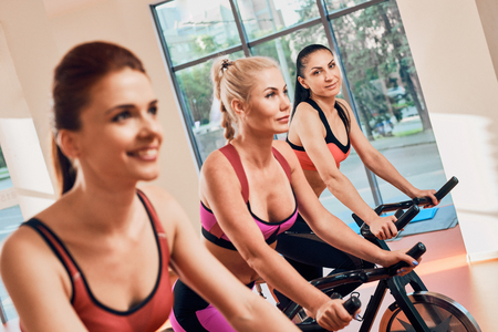 Young women exercising on stationary bicycles in fitness gym. focus on the girl away Stock Photo