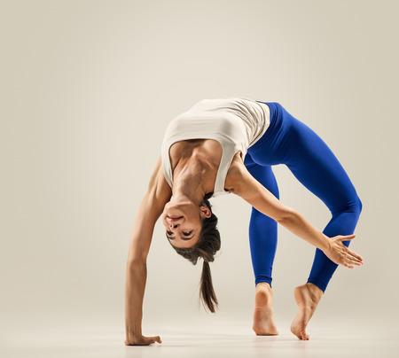 dhanurasana: Young woman doing Yoga exercises. studio. Bridge pose - Urdhva Dhanurasana Stock Photo