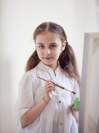 HI: Long-haired girl artist about canvas with brushes Stock Photo